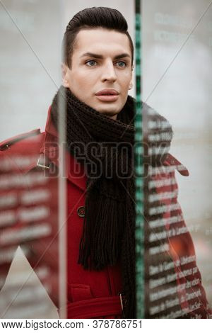 LGBTQ community lifestyle concept. Young homosexual man stands behind glass. Handsome fashionable gay male model poses in cityscape outdoors. Wears red coat, gloves, and black scarf.