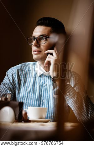 LGBTQ community lifestyle concept. Young homosexual man sits at the table in old-fashioned city cafe. Handsome gay male businessman talks on a phone while having a break at lunch.