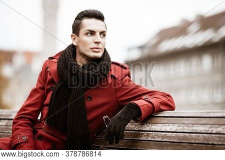 LGBTQ community lifestyle concept. Young homosexual man sits on bench in city park. Handsome fashionable gay male model poses in cityscape outdoors. Wears red coat, gloves, and black scarf.