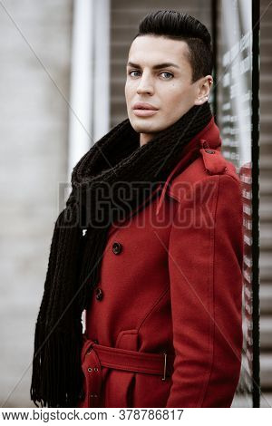 LGBTQ community lifestyle concept. Young homosexual man stands near glass. Handsome fashionable gay male model poses in cityscape outdoors. Wears red coat, gloves, and black scarf.