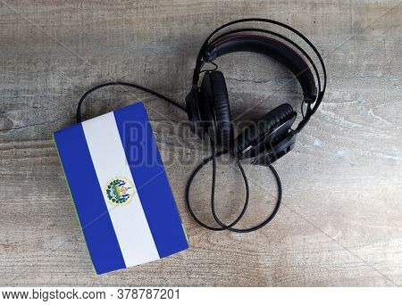 Headphones And Book. The Book Has A Cover In The Form Of Salvador Flag. Concept Audiobooks. Learning