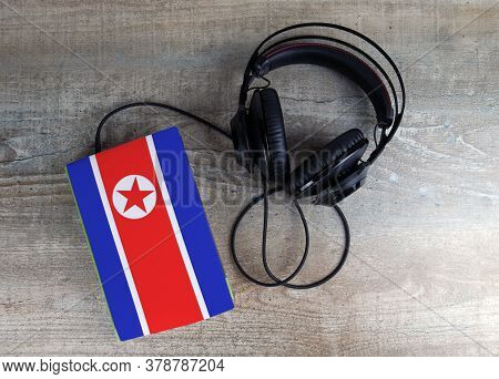 Headphones And Book. The Book Has A Cover In The Form Of North Korea Flag. Concept Audiobooks. Learn