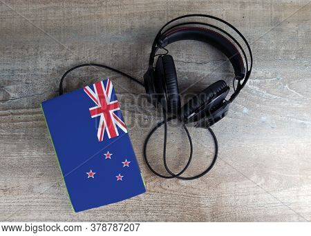 Headphones And Book. The Book Has A Cover In The Form Of New Zealand Flag. Concept Audiobooks. Learn