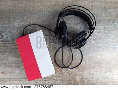 Headphones And Book. The Book Has A Cover In The Form Of Poland Flag. Concept Audiobooks. Learning L