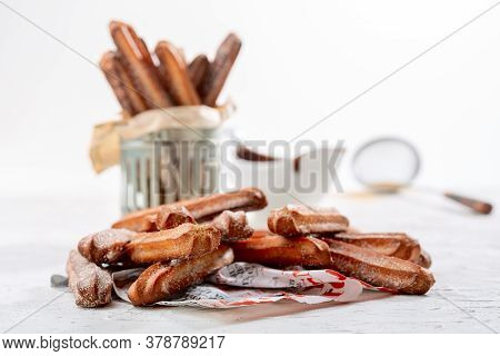 Churros With Cinnamon Sugar On A Paper Sheet And Chocolate Sauce. Traditional Spanish Breakfast.