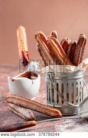 Churros With Sugar And Cinnamon In A Metal Cup And A Stick Of Churros In Melted Chocolate Sauce, Sel