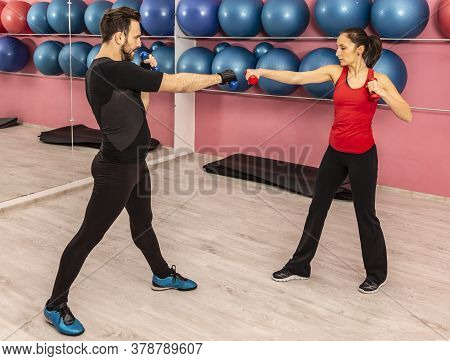 Image Of A Young Couple Doing Exercises With Dumbbels In A Gym