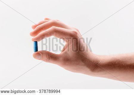 Hand Holding A Blue Capsule Pill, Isolated On White Background