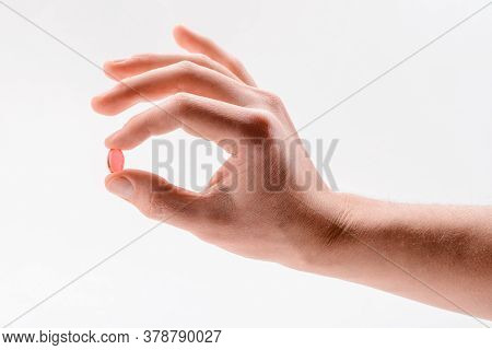 Hand Holding A Red Gel Capsule On White Background