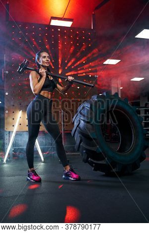 Front View Of Smiling Female Bodybuilder Posing In Gym, Having Rest After Hard Training, Red Lights.