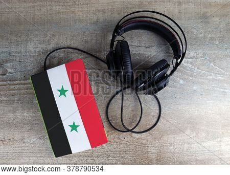 Headphones And Book. The Book Has A Cover In The Form Of Syria Flag. Concept Audiobooks. Learning La