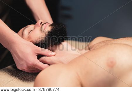 A Male Massage Therapist Makes A Client Athlete A Man A Neck Massage In A Dark Cozy Spa Massage Salo