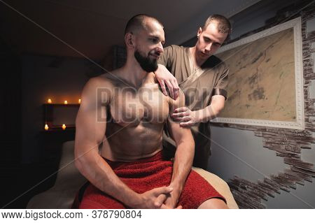 Male Masseur Does A Sports Shoulder Massage To A Muscular Male Athlete In A Room With A Contrasting
