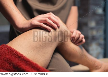 A Male Masseur Massages The Calf Muscle To A Male Athlete In A Professional Massage Salon. Sports Ma