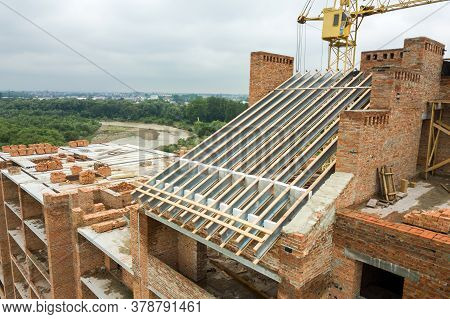 Aerial View Of Unfinished Brick Apartment Building With Wooden Roof Structure Under Construction.