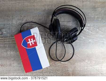 Headphones And Book. The Book Has A Cover In The Form Of Slovakia Flag. Concept Audiobooks. Learning