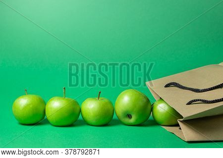 Green Apples On A Green Background. The Apples Fell Out Of The Paper Bag. Apples Are In A Line