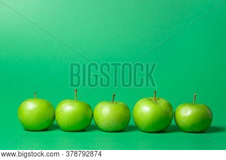 Green Apples On A Green Background. The Apples Are In A Line. Above There Is A Place For An Inscript