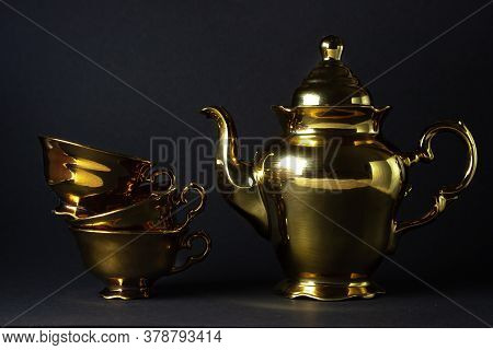 Gold Tea Set On A Black Background. Tea Cups Are Stacked On Top Of Each Other And There Is A Kettle