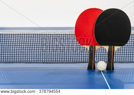 Black And Red Table Tennis Racket And A White Ball On The Blue Ping Pong Table With A Net, Two Table
