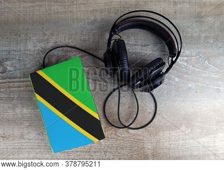 Headphones And Book. The Book Has A Cover In The Form Of Tanzania Flag. Concept Audiobooks. Learning
