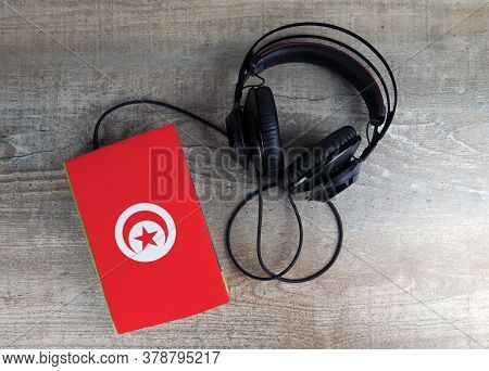 Headphones And Book. The Book Has A Cover In The Form Of Tunisia Flag. Concept Audiobooks. Learning