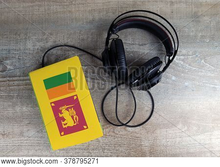 Headphones And Book. The Book Has A Cover In The Form Of Sri Lanka Flag. Concept Audiobooks. Learnin