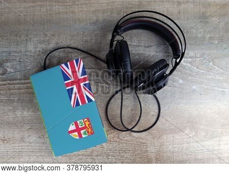 Headphones And Book. The Book Has A Cover In The Form Of Fiji Flag. Concept Audiobooks. Learning Lan