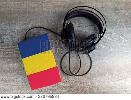 Headphones And Book. The Book Has A Cover In The Form Of Chad Flag. Concept Audiobooks. Learning Lan
