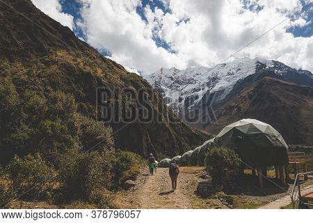 Two Persons Hiking Towards Salkantay Mountain Passing Near Sleeping Domes Camping