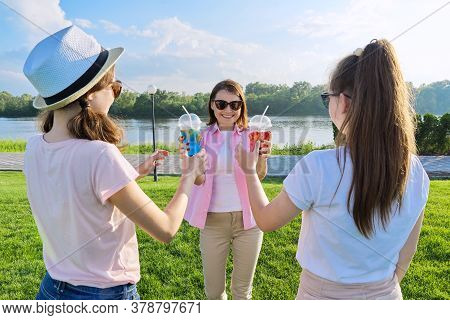 Portrait Of Happy Mother And Daughters Teenagers 14 And 16 Years Old, Girls With Summer Drinks. Back