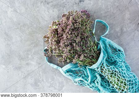 Alternative Medicine. A Bunch Of Dry Oregano Lies In A String Bag On The Table. Top View