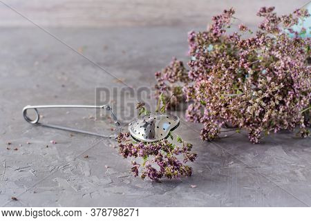 Herbal Treatment. A Bunch Of Oregano Is Clamped In A Teaspoon And A Bouquet Of Herbs Next To On The