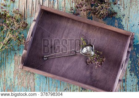 Herbal Treatment. A Bunch Of Oregano Clamped In A Teaspoon Lies In A Wooden Tray And Herbs Next To I
