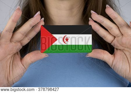 A Woman Shows A Business Card With An Image Of The Western Sahara Flag.