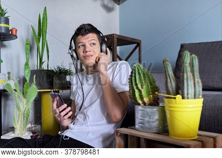Teenage Boy Hipster In Headphones With Smartphone Listening To Music, Home Interior Background. Teen