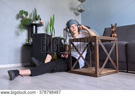 Teenage Boy Hipster In Headphones With Smartphone Listening To Music, Home Interior Background, Dog