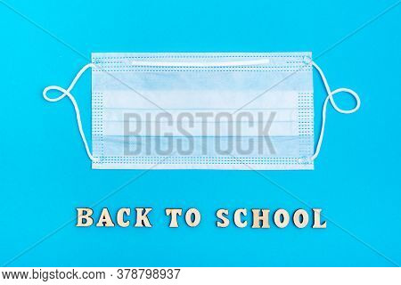 Back To School. The Inscription In Wooden Letters And A Protective Medical Mask On A Blue Background