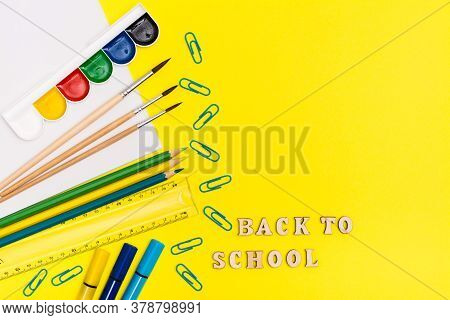 Back To School. Painting Supplies And Inscription In Wooden Letters On A Yellow Background. Top View