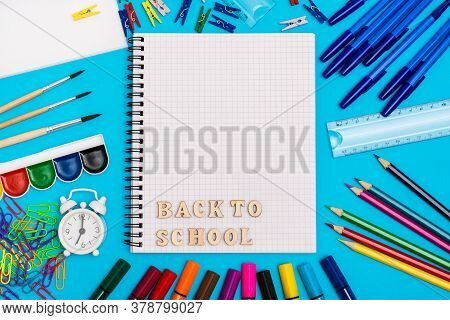 Back To School. Stationery, Alarm Clock And Inscription In Wooden Letters In A Notebook On A Blue Ba
