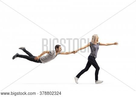 Young woman running and pulling a young man by the hand who is floating in air isolated on white background
