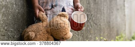 Panoramic Crop Of Beggar African American Child Holding Teddy Bear While Begging Alms On Urban Stree