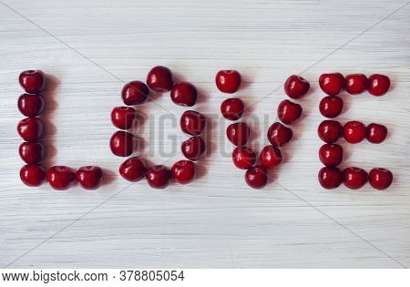 Red Cherry On A White Background, The Inscription Love, The Word Love Was Created From Sweet Cherry,