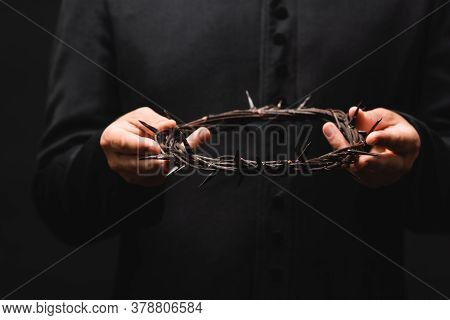 Cropped View Of Priest Holding Wreath With Spikes Isolated On Black