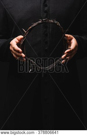 Cropped View Of Pastor Holding Wreath With Spikes Isolated On Black