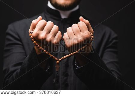 Selective Focus Of Pastor Holding Rosary Beads In Hands And Praying Isolated On Black