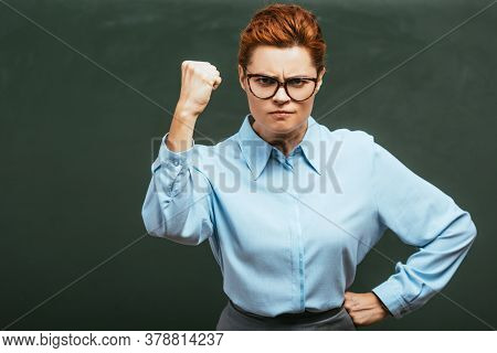 Irritated Teacher Showing Clenched Fist While Standing With Hand On Hip Near Chalkboard