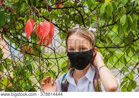 Schoolgirl Girl In A Black Protective Mask With A Backpack.