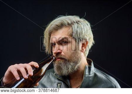 Handsome Bearded Male In Leather Jacket Drinks Craft Bottled Beer. Bearded Man Holds Bottle Of Bever