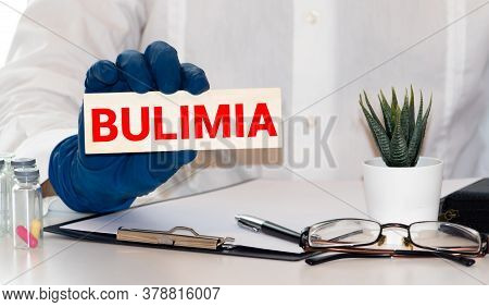 Woman Hand Holding Card With The Text Bulimia, Cutting The Word . Healthcare Concept. Retro Style